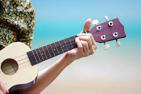 acoustic ukulele: hand picking Guitar ,Ukulele on the beach  Stock Photo