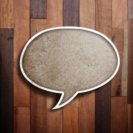 paper speech bubble on wood background  photo