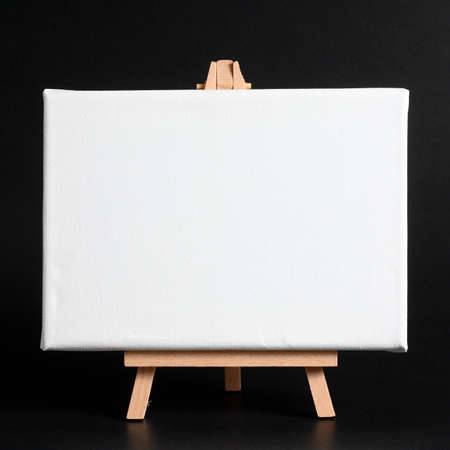 Cavalletto di legno con tela bianca su uno sfondo scuro