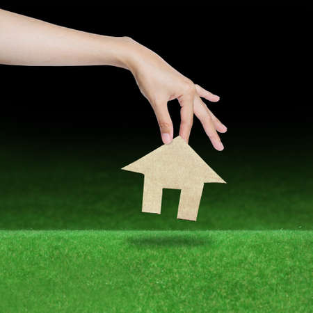hand picking paper house over grass field Stock Photo - 14459705