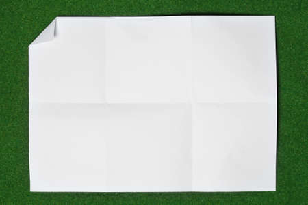 annoucement: paper folded and wrinkled on grass