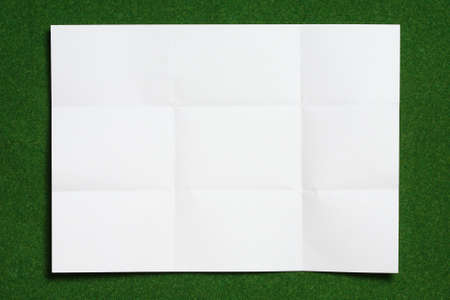 annoucement: paper folded and wrinkled on grass background