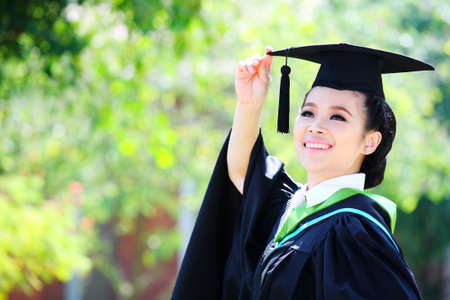 Portrait of a graduation female student looking up outdoors  photo
