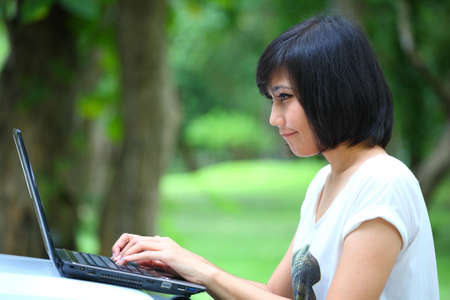young beautiful asian girl with laptop computer in her hands photo