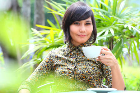 female drinking hot beverage in park-outdoor  photo