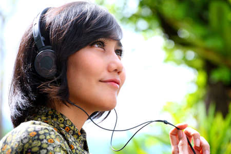 smiling female listening the music with headphone  photo