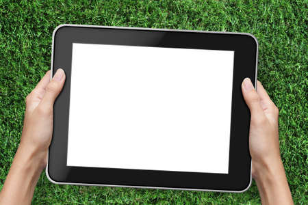 games hand: Hand holding tablet pc  over green grass background