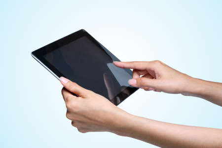 female hands holding a tablet pc  on blue background Stock Photo