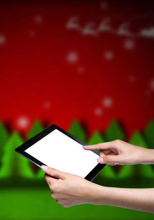 female hand pointing on tablet with red christmas background photo