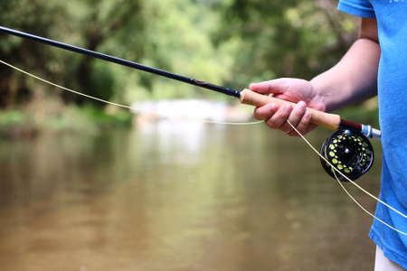 hand line fishing: fly fishing rod in hand