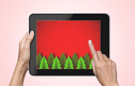 Christmas background on tablet pc  with female hand touch screen  photo