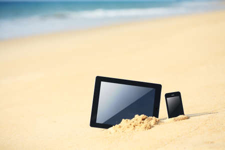 tablet and smartphone on the beach