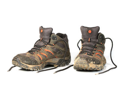 muddy clothes: dirty trekking boots over white background