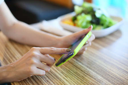 female using mobile phone on food table photo