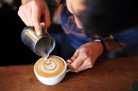 Barista pouring Latte art coffee close up. Stockfoto