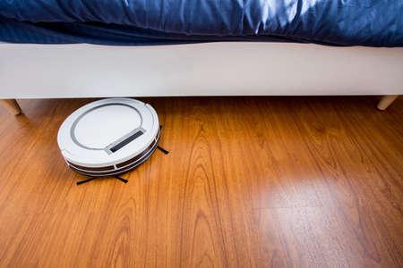 Robotic Vacuum Cleaner On Laminate Wood Floor In Bedroom Stock