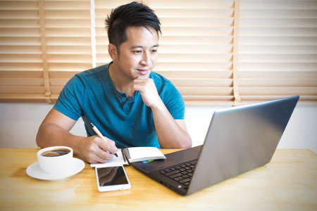 Young man wearing casual cothes working at home. Stock Photo