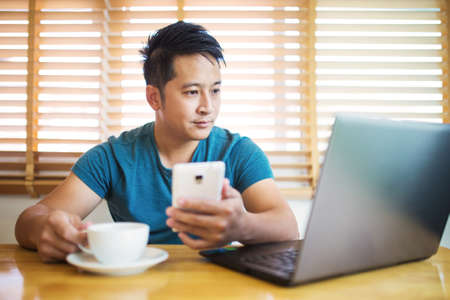 work at home: Young man wearing casual cothes working at home. Stock Photo