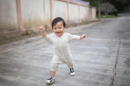 rozradostněný: Malý chlapeček chodí po ulici.