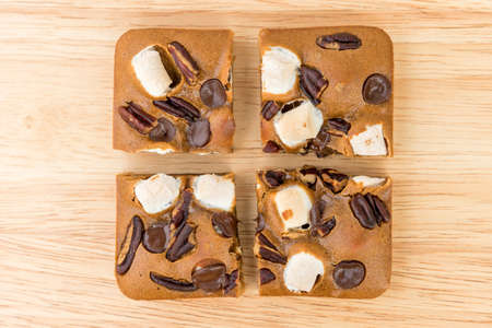 Blondie cake with marshmallow and dark chocolate on wood plate. Stock Photo