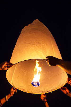 Hands praying while releasing paper Yee-Peng flying lantern in Kra thong festival, Chiang Mai, Thailand. Banque d'images