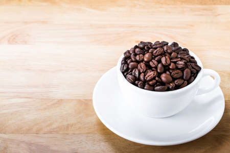 Coffee beans in white cup on wooden table. Foto de archivo