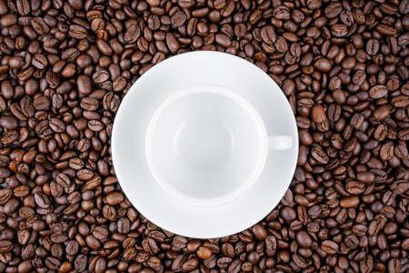 Empty coffee cup on coffee beans background. Foto de archivo