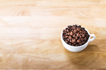 Coffee beans in white cup on wooden table. Banque d'images
