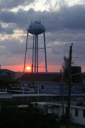 A view of the setting sun through a water tower Stock Photo