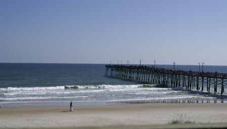 topsail: A couple walking on the beach with a view of the pier