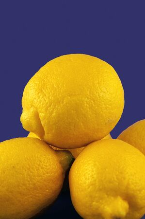 A pile of yellow lemons against a blue background