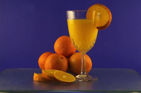 Oranges and orange juice against a blue background Stock Photo