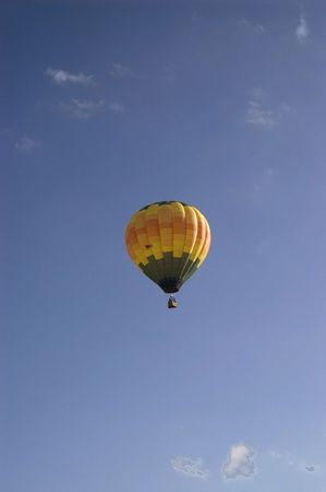 A vertical image of a floating hot air balloon.