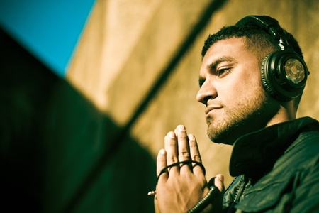 Buddhist DJ praying in sunlight of urban alley. Model is 'DJ Budi', and produces his own electronic music in Worcester, MA. https://www.facebook.com/TheDJBuDi