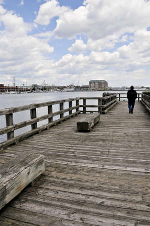 In the distance a man is walking on a long wharf in Boston, Massachusetts