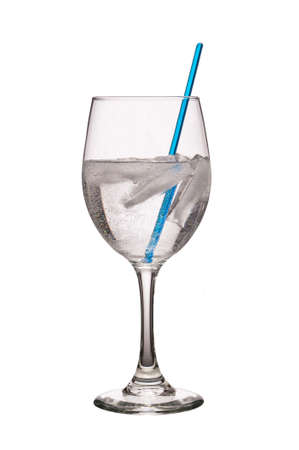 Glass filled with clear carbonated liquid and ice cubes with blue stir rod isolated on a pure white background Stock fotó