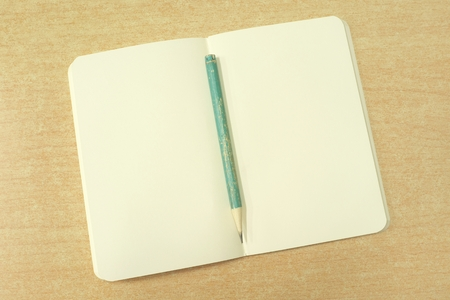 Open notebook with pale yellow pages and old green pencil on wooden desk photo