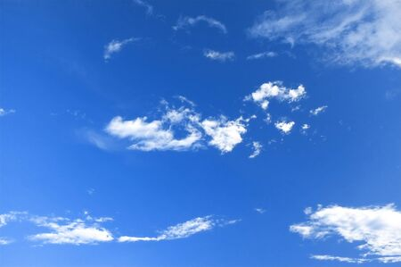 Bright blue sky with small white fluffy clouds photo