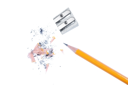Sharpened yellow pencil with a metal pencil sharpener and shavings isolated on a white background. Imagens
