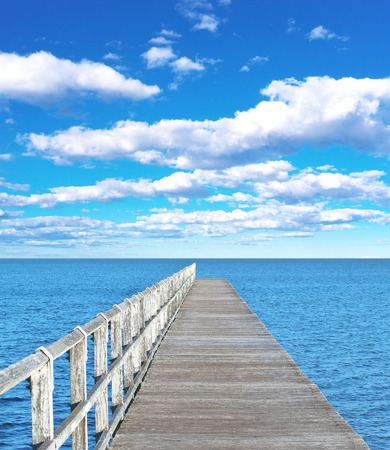 Long wooden pier and cloudy sky horizon Imagens