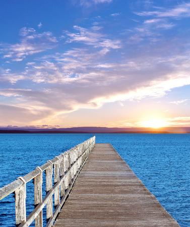 long wooden pier and sunset horizon Imagens