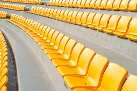 rows of empty yellow stadium seats