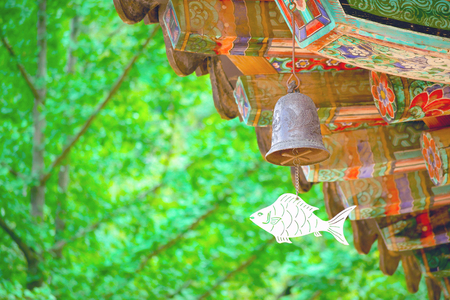 Buddhist bell with fish symbol hanging from temple eaves against natural green background Korea South
