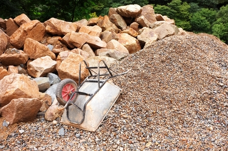 upturned metal wheelbarrow on pile of gravel with large boulders in background