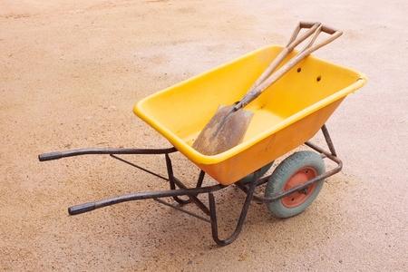 yellow wheelbarrow with two spades Imagens