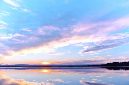 sunset sky over a lake Imagens