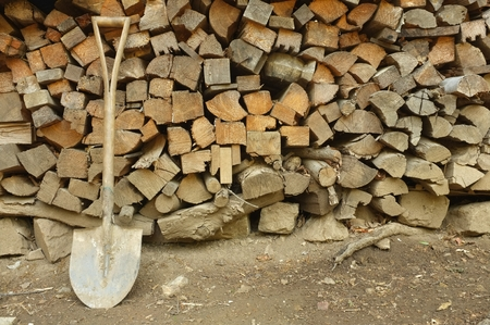 metal spade leaning on stack of fire wood