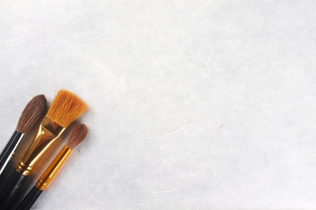 paintbrushes on rice paper textured background Imagens