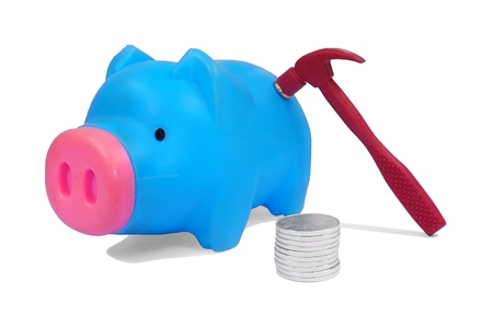 plastic piggy bank with stack of coins and hammer