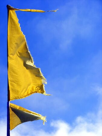 Yellow flag waving in the wind. Stock Photo